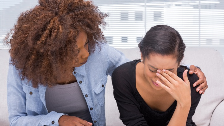 Sad woman crying next to her therapist who is comforting her